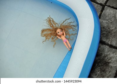 naked children's doll with Long blond hair Floating in Swimming pool
