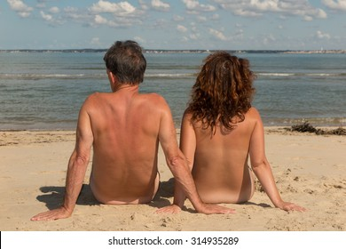 Naked couple sitting on the beach.