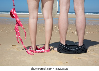 Naked couple standing on the beach with their swimwear on their feet