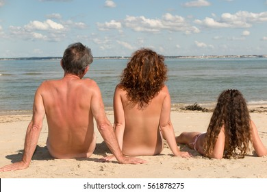 Naked family sitting on the beach composed father mother and daughter naturism