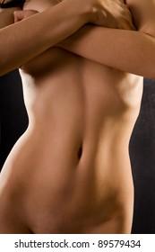naked female body on a black background