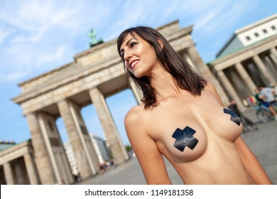 Naked girl with black tape stripes stands on Brandenburger Tor in Berlin / Germany