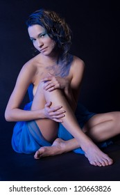 Naked girl in a blue cloth. studio portrait