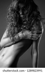 naked girl with frizzle Hairdo. Black and white Portrait of nude sexy Beautiful young woman, curl hairstyle