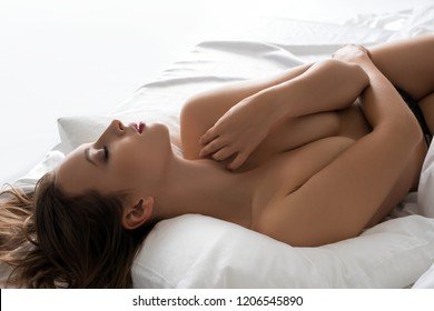 Naked girl lying in bed isolated cropped view