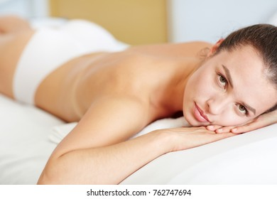 Naked girl lying in spa salon and relaxing before body massage