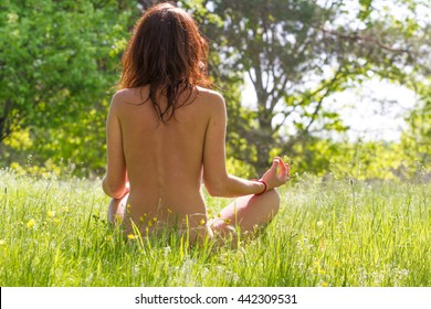 Naked girl make yoga exercises in park. Meditation and concentration. Namaste