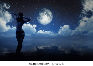 naked girl on sea beach looking at moon