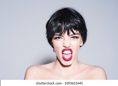 Naked girl with red lips wearing black wig isolated on gray background. Portrait of young woman with impudent, violent face, mental health issues concept.
