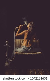 naked girl smoking hookah, pretty woman with sexy back and body in jeans sitting on eastern chair on wooden floor with shisha, bong or kalian as arabic tradition on black background