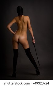 naked girl with a whip in a mask and stockings in high-heeled shoes stands with her back