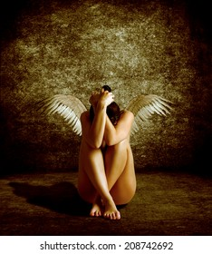 Naked girl with wings on his back sits burying its head. Fallen Angel.
