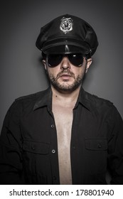 Naked, Good looking policeman, sexy police with sunglasses over dark background