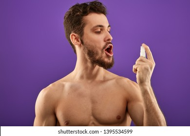 naked guy using mouth freshner. medicine, business concept. man having problems with breath. spray for throat. guy treating his throat with spray.