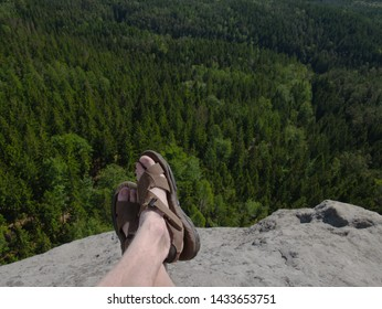 Naked hairy male legs with leather sandals rest while trail. Person enjoy fantastic view into wild landscape and gains again power.