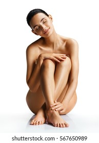 Naked lady gets Spa treatments sitting on white background. Photo of beautiful woman with perfect skin. Wellness and Spa concept.