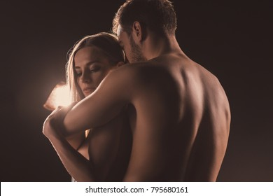 naked lovers hugging, on brown with back light