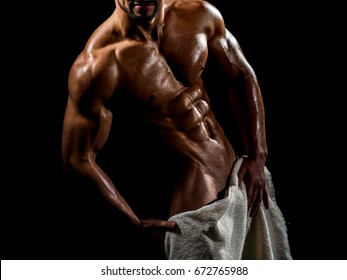 Naked male body with towel, sexy guy covered genitals with white towel in shower. Athlete ideal body, lover. Man bodybuilder torso. Muscular guy athletic, biceps, shoulders, chest, abs, six pack