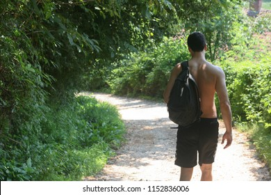 Naked man with backpack hiking