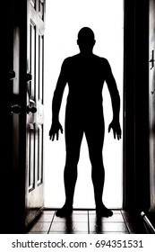 Naked man at doorway threshold in silhouette, white background