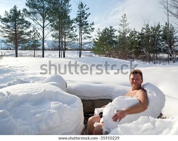 Naked man enjoying snow outdoor after hot sauna. Healthy treatment. Winter.