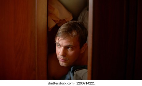 the naked man is hiding in the wardrobe. he goes out of the closet and runs away from the mistress's house through the front door.