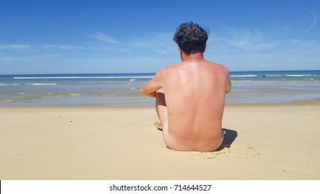 Naked man nude sit on the beach in summer