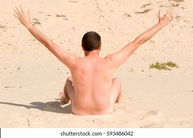 naked man on the nudist beach spreads out the arms of victory