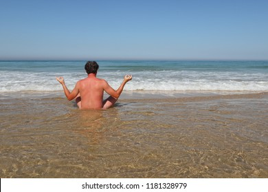 naked man on water beach make yoga in back view in summer day