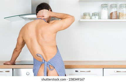 Naked man preparing food in the kitchen. View from the back.