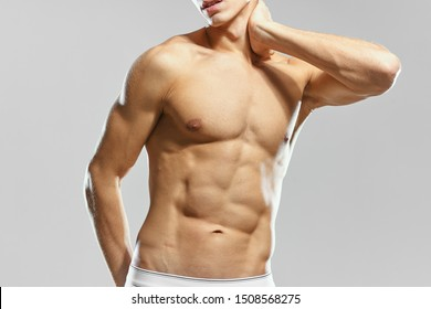 Naked man with a pumped-up torso on a gray background cropped view of a bodybuilder