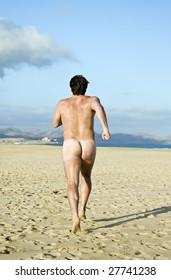 A naked man running on beach.
