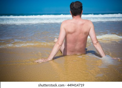 Naked man is sitting cross legged on an empty beach and meditating.