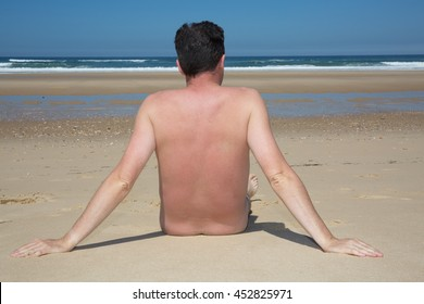 A naked man is sitting on an empty beach relaxing
