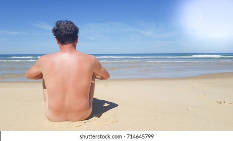A naked man sitting on empty beach