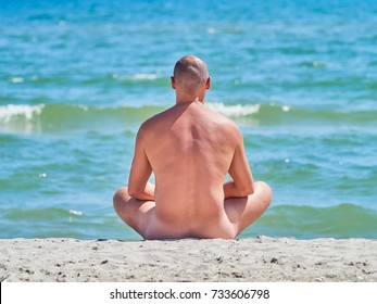 A naked man is sitting on an empty beach and meditating.