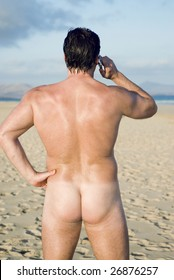 A naked man is standing on an empty beach and using his cellphone.