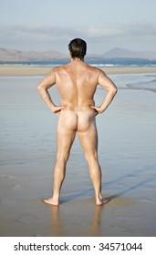 A naked man standing on empty beach.