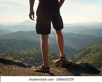 Naked man stay in black pants only at the top of the mountain. Hiker watch the morning hilly landscape and thinking.