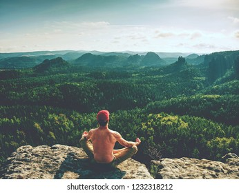 Naked man in yoga lotus pose for breathing, meditating and relaxing. Sportsman doing an Yoga Exercise Sitting against