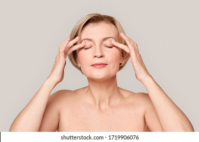 Naked mature woman standing isolated on grey background beauty concept close-up applying eye cream on eyelids pensive
