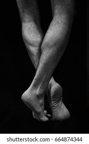 Naked muscular male legs on a black background. Contrast black and white photo