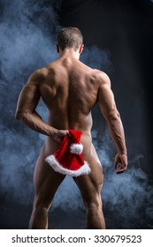 Naked Muscular Man Posing in Studio with Dark Background Covering Bottocks Area with Santa Hat