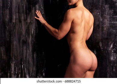 Naked muscular strong woman on a dark background