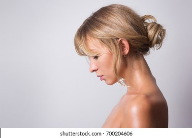Naked natural woman oiled body with healthy skin. Slim blond woman. Spa and wellness concept.
