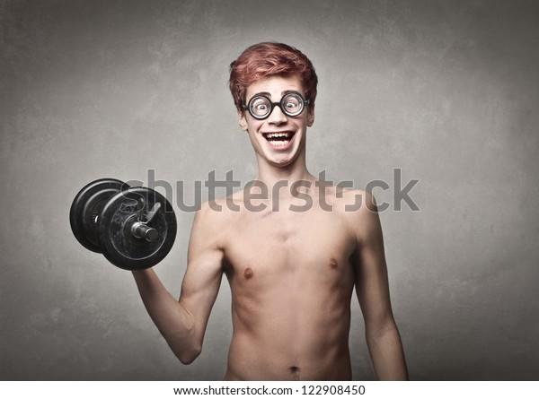 Naked nerd guy raising a dumbbell