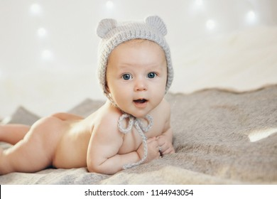 naked newborn baby lying on his tummy in a knitted hat. Little boy on white background