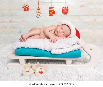naked newborn baby in red hat sleeping on sledge-cot