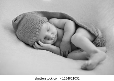 a naked newborn baby sleeps in a Christmas hat.