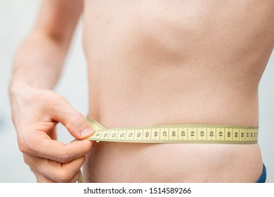 naked person with centimeter measuring the body size. diet concept